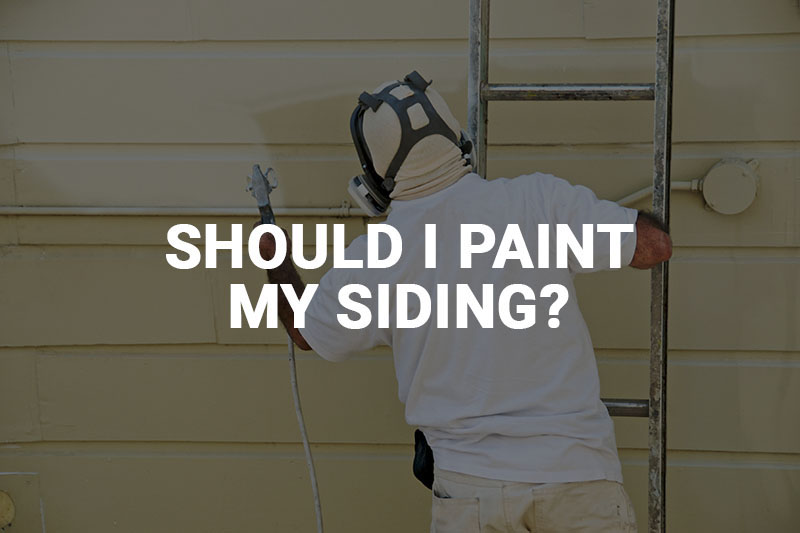 Worker painting siding